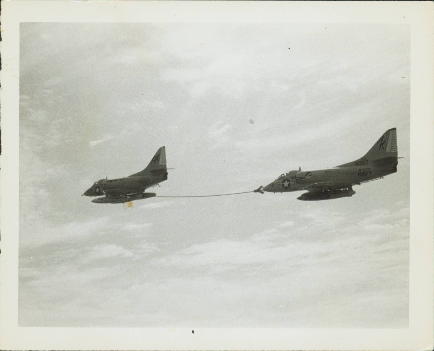 A photo of the side view of two flying jet planes connected by a fuel line from the back of one plane to the front of the other.