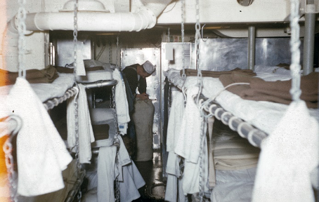 Color photo of berthing racks with unmade beds and towels hung around chains, a sailor in the background bends over a sea bag.
