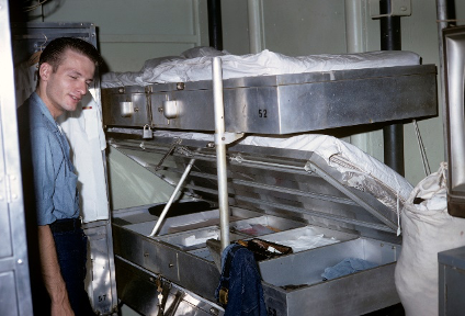 Color photo of sailor standing next to bunk, the middle bunk is open to reveal a locker and storage compartments below.