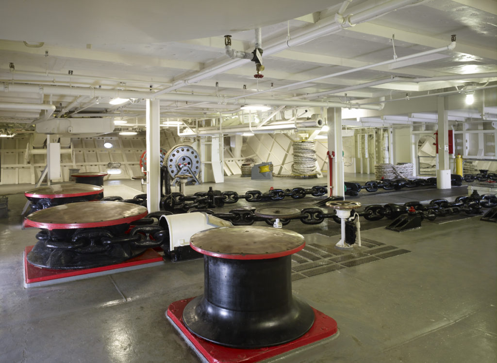 Color photograph of Intrepid's anchor chain room showing cylindrical capstans and large, black chains stretched across the deck