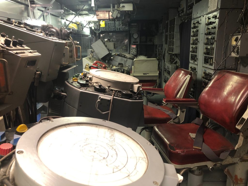 Color photograph of Intrepid's combat information center showing two radar sets and two red chairs, along with other equipment.