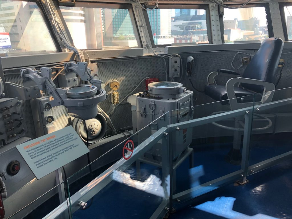 Color photograph of Intrepid's flag bridge, with windows that overlook the flight deck and the city beyond. The admiral's blue chair is at the right, and navigation equipment is at center.