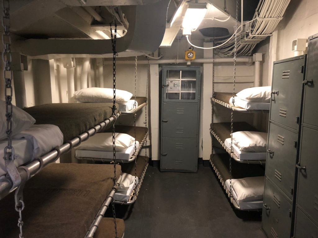Color photograph of Marine berthing on board Intrepid. A locker is in the background at the center of the image, with other lockers at left. Bunks stacked three high are on either side of the central locker.