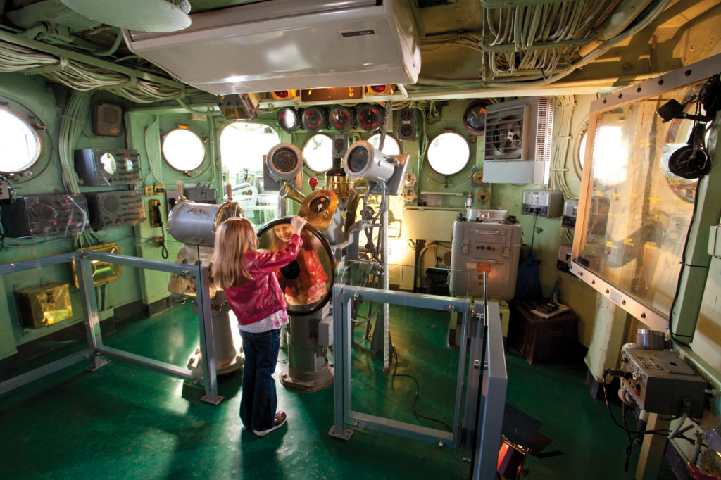 Color photograph of the pilot house on board Intrepid. A child turns the ship's wheel at the center of the photograph. A plotting board hangs at right.