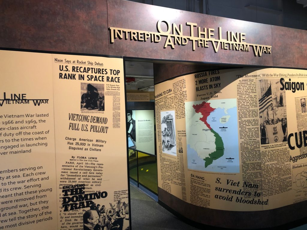 Color photograph of the entrance to the exhibition On the Line: Intrepid and the Vietnam War. The entranceway at center is flanked by reproductions of period newspaper headlines and a map of Vietnam. The exhibition title is over the entranceway.
