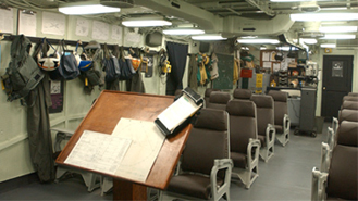 Color photograph of a ready room on board Intrepid. A podium stands at the center of the image, with rows of brown chairs facing it. Helmets, flight suits and other pilot items hang on the walls around the room.