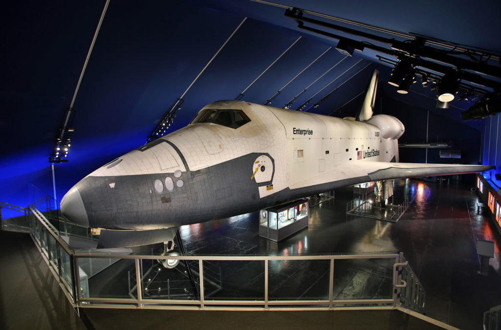 Color photograph of the space shuttle orbiter Enterprise on display at the Intrepid Sea, Air & Space Museum. The nose of the black and white shuttle points to the right. The walls and ceiling of the Space Shuttle Pavilion are dark blue.