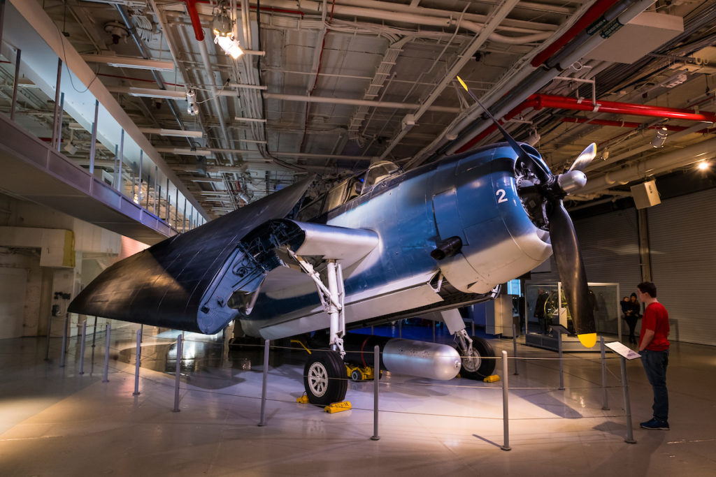 TBM Avenger on display on the hangar deck at the Intrepid Sea, Air & Space Museum. The propeller-driven airplane is blue and white, and its wings are folded. A torpedo is displayed under the airplane. A person looks at the airplane.