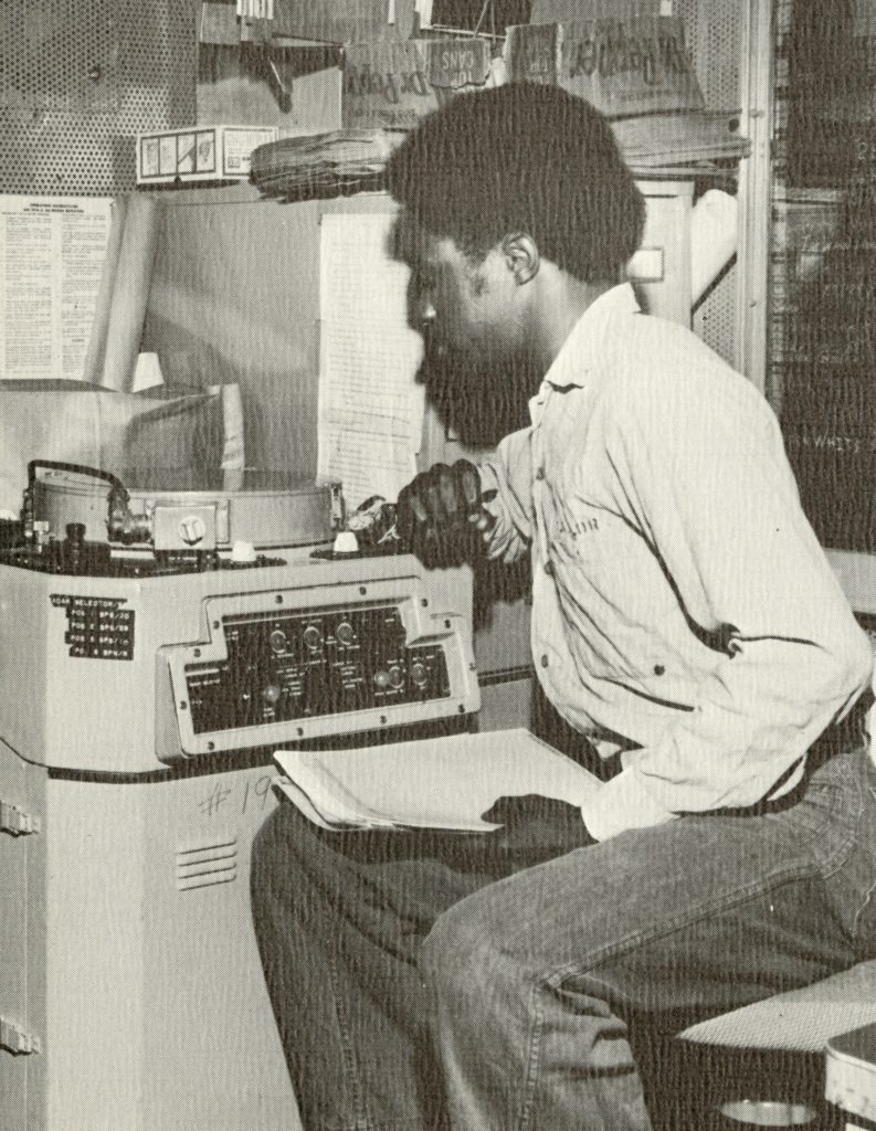 Black and white image of a man seated and looking at radar equipment, holding papers in his left hand.